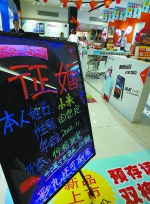 """小米的时尚营销一直为商家所称道。图为广州一家商城为小米手机打出雷人""""征婚启事,彩礼倒贴""""的广告吸引顾客。"""